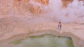 Den unga eleganta kvinnan går till sjön i bergen mot en vit rök flyg- sikt