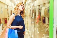 Den unga eleganta kvinnan som in ser, shoppar fönstret Royaltyfri Foto
