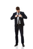 Den unga eleganta mannen binder slipsen royaltyfria foton