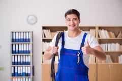 Den unga elektrikeren med kabel som i regeringsställning arbetar royaltyfria foton