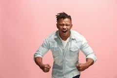 Den unga emotionella ilskna afro mannen som skriker på rosa studiobakgrund Arkivbild