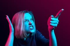 Den unga emotionella ilskna kvinnan som skriker på neonstudiobakgrund arkivfoton