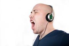 Den unga emotionella mannen lyssnar till musik Royaltyfri Foto