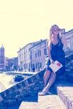 Den unga enkla kvinnliga turisten i en gammal italiensk stad kallade Comacchio den retro stil filtrerade bilden Royaltyfri Bild