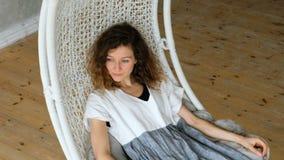 Den unga europeiska flickan i en linneklänning svänger i engunga i en vindlägenhet Härlig kvinna som vilar i en hängmatta stock video