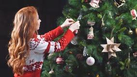Den unga förföriska flickan i röd tröja dekorerade trädet arkivfilmer