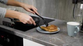 Den unga försiktiga kvinnan tar pannkakor från pannan och sätter på en platta på köksbordet i morgontid lager videofilmer