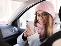 Den unga förtjusande blonda kvinnan i rosa färger stuckit hatthalsduksammanträde i bil med telefonen i hand övervintrar utomhus arkivfoton