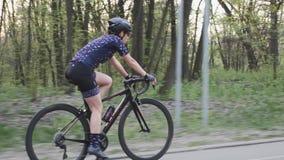 Den unga f?rdiga kvinnaridningcykeln i parkerar Sun till och med trees F?lj skottet l?ngsam r?relse lager videofilmer