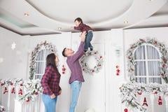 Den unga fadern kastar upp den lilla sonen med modern i juldekor royaltyfri bild