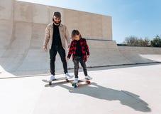 Den unga fadern och hans sonrittskateboarder i en skridsko parkerar med glidbanor som är utvändiga på den soliga dagen royaltyfri foto