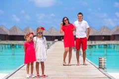 Den unga familjen av fyra har gyckel på träbryggan fotografering för bildbyråer