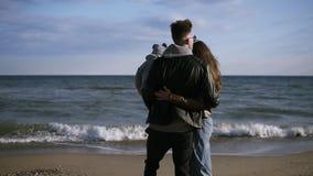 Den unga familjen, en fader med hans son på hans armar, promenerar kusten av swaen, på den lyckliga familjen för kust A går arkivfilmer