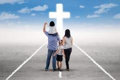 Den unga familjen följer ett kors på vägen Arkivfoto