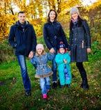 Den unga familjen, föräldrar med småbarn i guld- höststad parkerar fotografering för bildbyråer