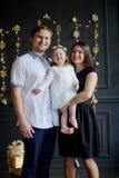 Den unga familjen fotograferas för julkortet arkivfoto