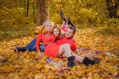 Den unga familjen har gyckel på plädet i solig varm höstdag arkivfoton