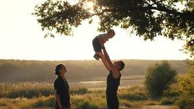 Den unga familjen med behandla som ett barn på solnedgång lager videofilmer