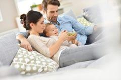 Den unga familjen med behandla som ett barn på hållande ögonen på tv för soffan Royaltyfria Foton