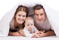 Den unga familjen med behandla som ett barn pojken under filten på säng Arkivbild