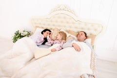 Den unga familjen med dotterlögn i vitt rum på säng, flicka vaknade u Royaltyfri Foto