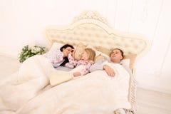 Den unga familjen med dotterlögn i vitt rum på säng, flicka vaknade u Royaltyfria Foton