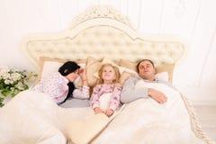 Den unga familjen med dotterlögn i vitt rum på säng, flicka vaknade u Fotografering för Bildbyråer