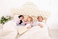 Den unga familjen med dotterlögn i vitt rum på säng, flicka vaknade u Arkivbilder