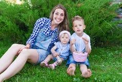 Den unga familjen med en korg av champinjoner i sommar parkerar Arkivbild