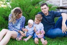 Den unga familjen med en korg av champinjoner i sommar parkerar Arkivbilder