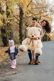 Den unga familjen med den lilla dottern på hösten parkerar närvarande bi för vägen royaltyfri fotografi