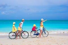 Den unga familjen med små ungar rider cyklar på en tropisk exotisk strand Arkivfoton