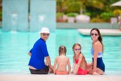 Den unga familjen med två ungar tycker om sommarsemester i utomhus- pöl Royaltyfria Bilder