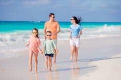 Den unga familjen på semester har gyckel på stranden arkivfoton