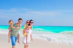 Den unga familjen på semester har mycket gyckel på stranden Royaltyfri Foto