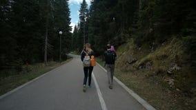 Den unga familjen promenerar landsvägen i hösteftermiddag stock video