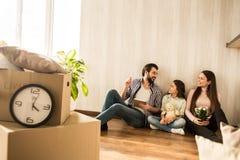 Den unga familjen sitter tillsammans på golvet i vardagsrummet De har precis att flytta sig in i denna lägenhet Flickor är fotografering för bildbyråer