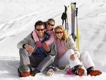 Den unga familjen skidar på semester Arkivbilder