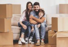 Den unga familjen som flyttar sig till det nya stället och, sitter på soffan Arkivbild
