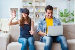 Den unga familjen som spelar lekar med virtuell verklighetexponeringsglas royaltyfria bilder