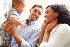 Den unga familjen som spelar med lyckligt, behandla som ett barn sonen hemma arkivfoton