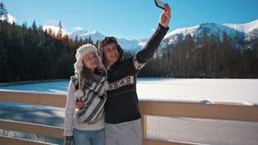 Den unga familjen tar Selfie vid Smartphone utomhus i berg i vinter stock video