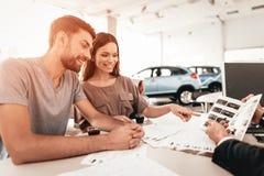 Den unga familjen väljer en ny bil i visningslokal arkivfoto