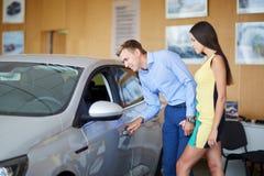 Den unga familjen väljer den nya bilen i en visningslokal bollar dimensionella tre Arkivfoton