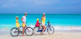 Den unga familjridningen cyklar på den tropiska stranden Fotografering för Bildbyråer
