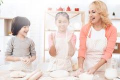 Den unga farmodern med små barnbarn skrattar i kök Stekheta kakor fotografering för bildbyråer