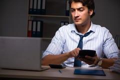 Den unga finansiella chefen som sent i regeringsställning arbetar på natten royaltyfria foton