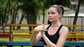Den unga flickan för idrotts- sportar utför en uppvärmning av händer på sportfältet i parkera lager videofilmer
