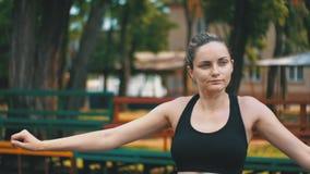 Den unga flickan för idrotts- sportar utför en uppvärmning av händer på sportfältet i parkera arkivfilmer
