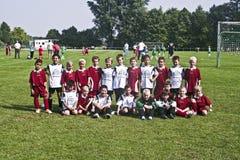 Den unga fotbollspelaren poserar proudly för Team Photo Royaltyfri Fotografi